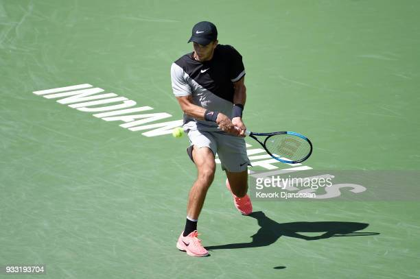 Borna Coric of Croatia hits a backhand against Roger Federer of Switzerland during the semifinal match on Day 13 of the BNP Paribas Open on March 17...