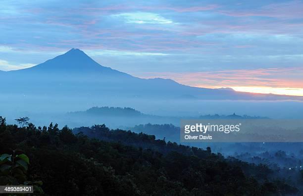 Borobudur Temple on ridge, Merapi Volcano and surrounding valley draped in morning mists.