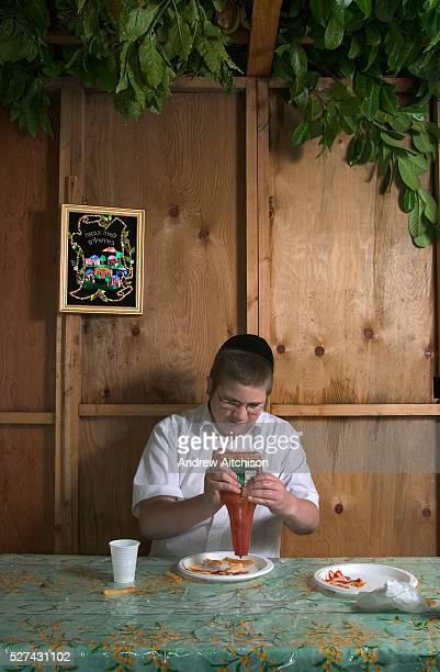 Boruch Shloima squeezing tomato sauce onto his take away chips whilst sitting in the family Sukkah during the festival of Sukkot the feast of...