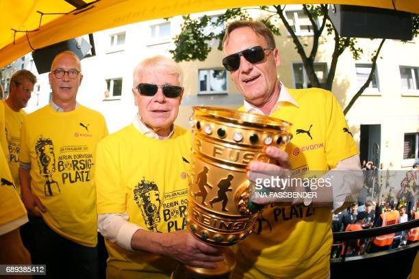 Borussia Dortmund CEO HansJoachim Watzke and Borussia Dortmund President Reinhard pose with the trophy as they arrive at Borsigplatz during...