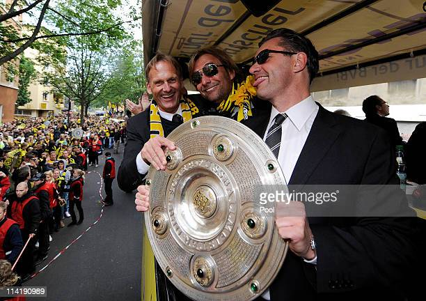 Borussia Dortmund CEO HansJoachim Watzke head coach Juergen Klopp and manager Michael Zorc celebrate with the trophy after winning the Bundesliga...