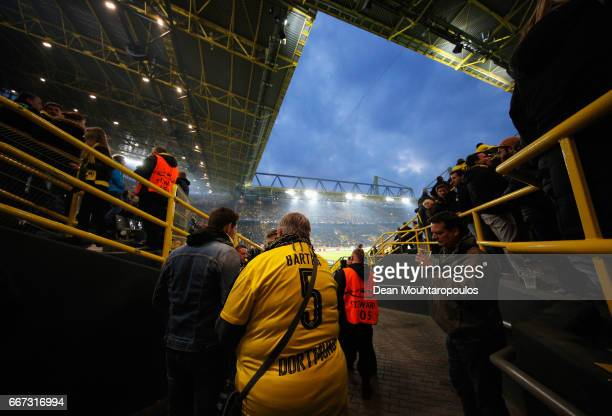 Borussia Dortmund fan in a Marc Bartra shirt waits for news inside the stadium after an explosion near the Borussia Dortmund team coach prior to the...