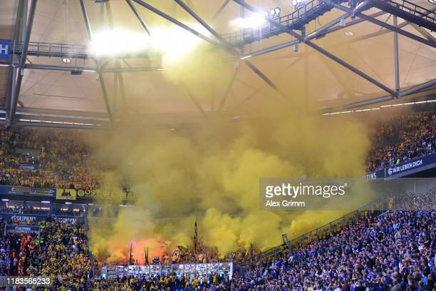 Borussia Dortmund fans let off smoke flares during the Bundesliga match between FC Schalke 04 and Borussia Dortmund at VeltinsArena on October 26...