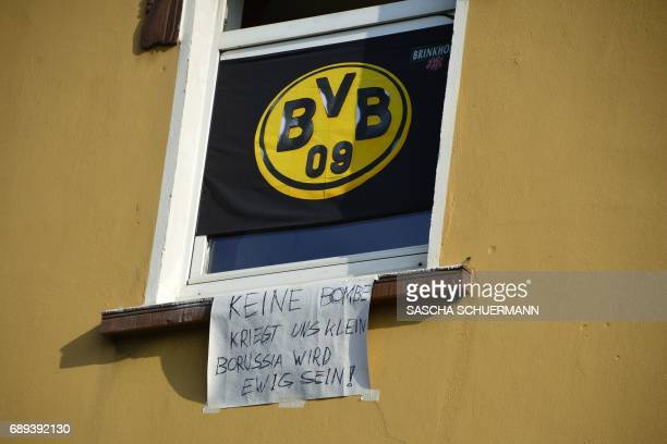 A Borussia Dortmund flag and a sign reading 'No bomb will make us small Borussia will live for ever' ahead of celebrations after winning the German...