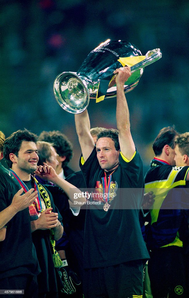 Borussia Dortmund player Paul Lambert raises the trophy after the UEFA Champions League final between Borussia Dortmund and Juventus at the Olympic Stadium on May 28, 1997 in Munich, Germany.
