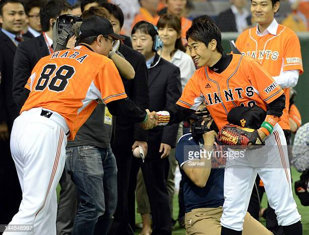 Borussia Dortmund player Shinji Kagawa shake hands with Yomiuri Giants head coach Tatsunori Hara after throwing the memorial first pitch prior to the...