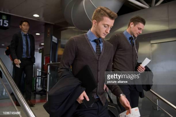 Borussia Dortmund players Shinji Kagawa Marco Reus and Lukasz Piszczek head towards their gate in the airport in Lisbon Portugal 15 February 2017 The...