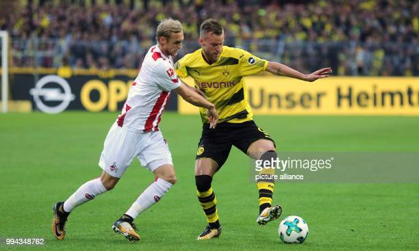 Borussia Dortmund's Andrej Yarmolenko and FC Cologne's Marcel Risse vie for the ball during the German Bundesliga soccer match at the Signal Iduna...