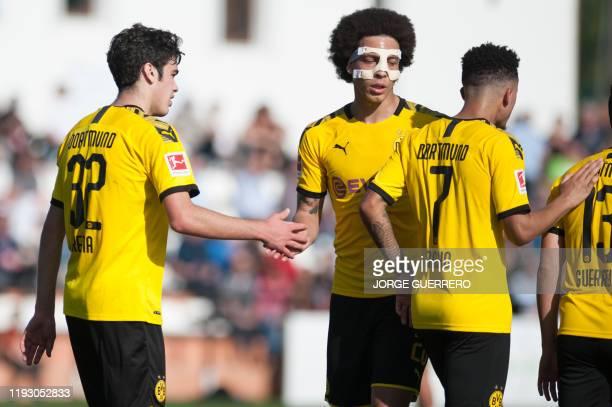 Borussia Dortmund's British midfielder Giovanni Reyna celebrates with Belgian midfielder Axel Witsel after scoring during the friendly football match...