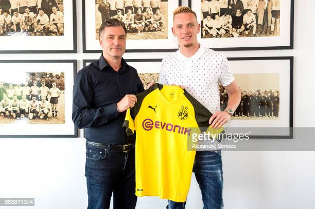 Borussia Dortmund's head of sport Michael Zorc and newly signed player Marius Wolf pose for a photo at Borussia Dortmund main office on May 28 2018...