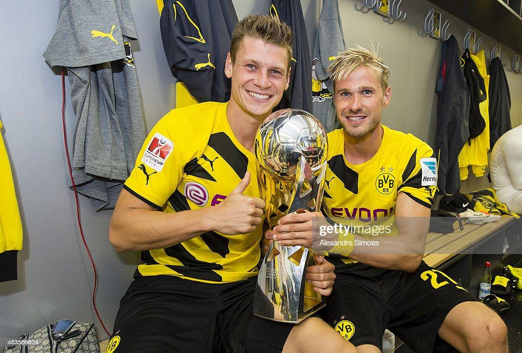 Borussia Dortmund's Lukasz Piszczek and Oliver Kirch celebrate winning the SuperCup trophy in the changing room after the DFL Supercup match between Borussia Dortmund and FC Bayern Muenchen at Signal Iduna Park on August 13, 2014 in Dortmund, Germany.