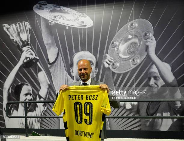 Borussia Dortmund's new coach Dutch Peter Bosz poses with a jersey after a press conference on June 6 2017 in Dortmund Briefly a player in Germany...