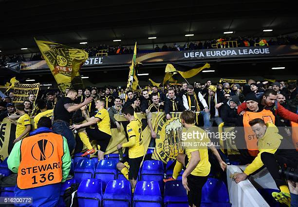 Borussia Dortmund's players celebrate with their supporters in the stands after the UEFA Europa League round of 16 second leg football match between...