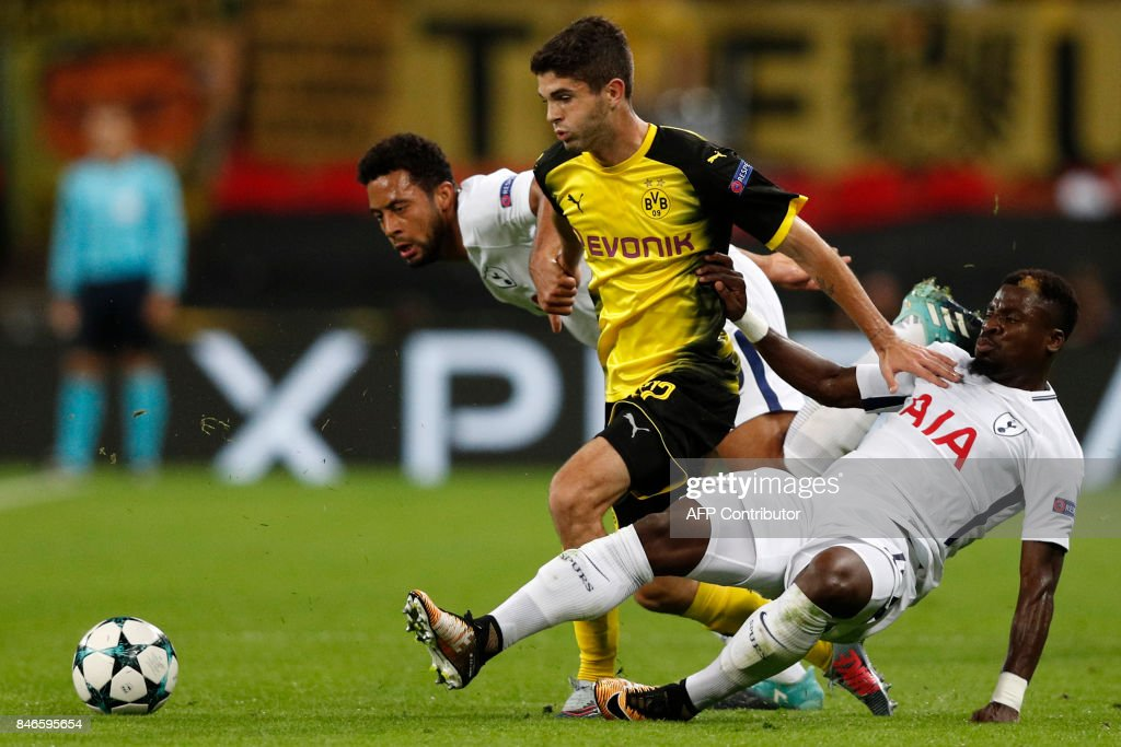 Borussia Dortmund's US midfielder Christian Pulisic (C) vies with Tottenham Hotspur's Belgian midfielder Mousa Dembele (L) and Tottenham Hotspur's Ivorian defender Serge Aurier (R) during the UEFA Champions League Group H football match between Tottenham Hotspur and Borussia Dortmund at Wembley Stadium in London, on September 13, 2017. Tottenham won the game 3-1. / AFP PHOTO / Adrian DENNIS