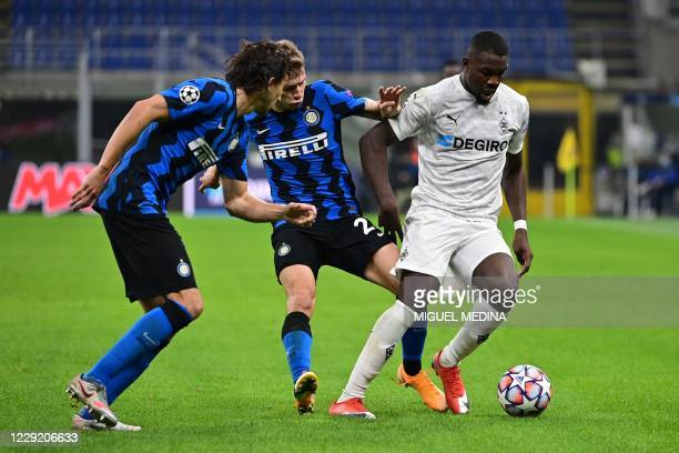 Borussia Moenchengladbach's French forward Marcus Thuram fights for the ball with Inter Milan's Italian defender Matteo Darmian and Inter Milan's...