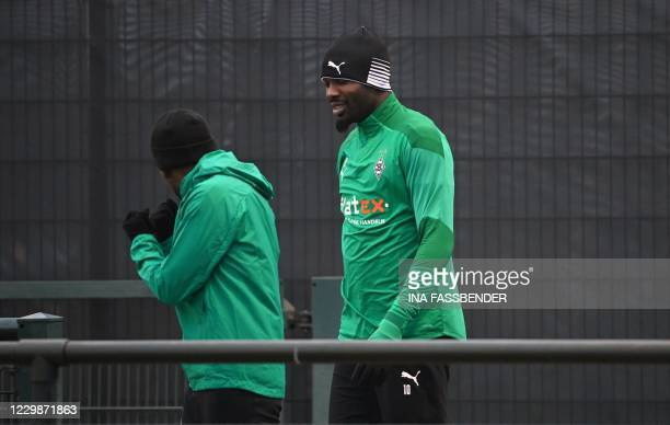 Borussia Moenchengladbach's Guinean midfielder Ibrahima Traore and Borussia Moenchengladbach's French forward Marcus Thuram arrive for the training...