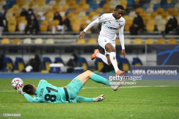 Borussia Moenchengladbach's Guinean midfielder Ibrahima Traore is challenged by Shakhtar Donetsk's Ukrainian goalkeeper Anatolii Trubin during the...