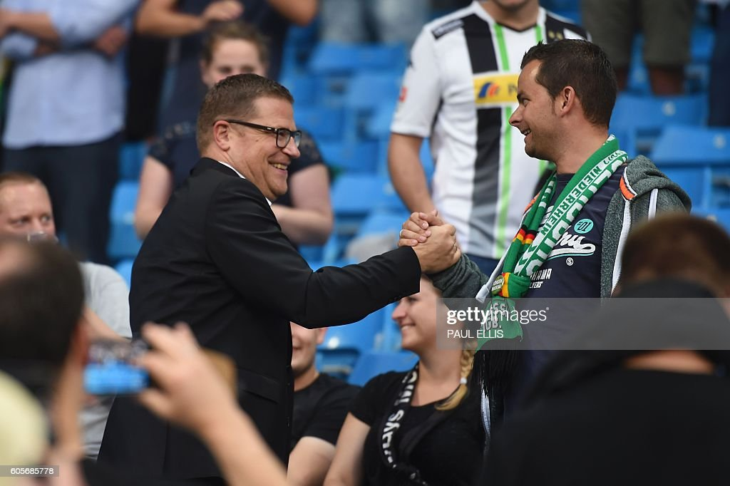 Borussia Monchengladbach's director of sport Max Eberl (L) shake hands with fans ahead of the UEFA Champions League group C football match between Manchester City and Borussia Monchengladbach at the Etihad stadium in Manchester, northwest England, on September 14, 2016. / AFP / PAUL