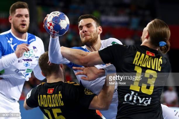 Borut Mackovsek of Slovenia is challenge by Igor Radojevic of Montenegro and Mirko Radovic of Montenegro during the Men's Handball European...