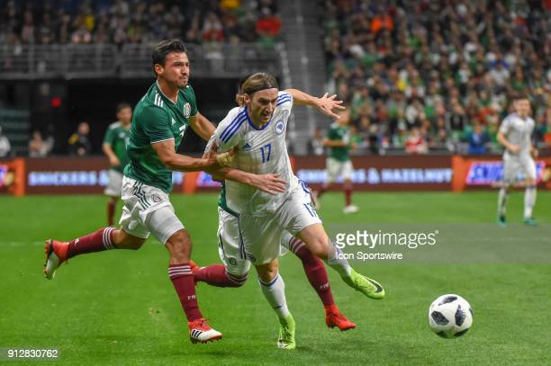 Bosnia and Herzegovina forward Mersudin Ahmetovic is pulled down by Mexico defender Oswaldo Aanis during the soccer match between Mexico and Bosnia...