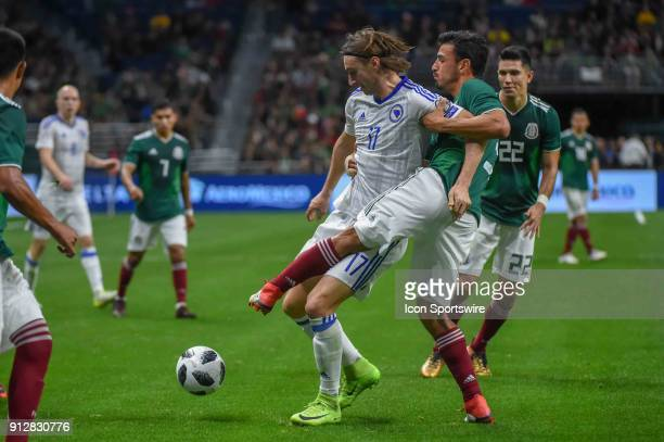 Bosnia and Herzegovina forward Mersudin Ahmetovic is pulled off the ball by Mexico defender Oswaldo Aanis during the soccer match between Mexico and...