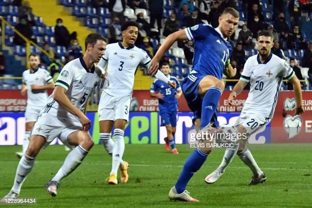 Bosnia and Herzegovina's forward Edin Dzeko controls the ball next to Northern Ireland's defender Craig Cathcart , Northern Ireland's defender Jamal...