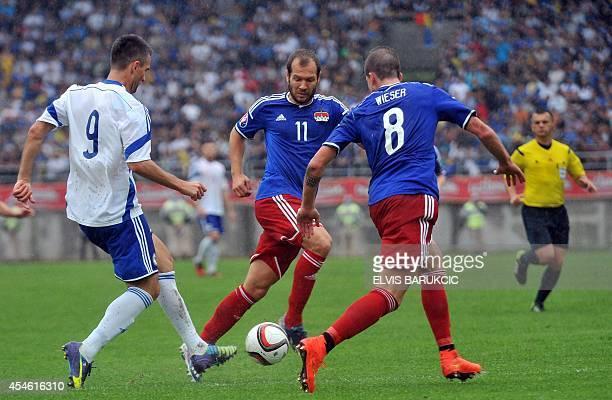 Bosnia and Herzegovina's Vedad Ibisevic vies with Liechtenstein's Franz Burgmeier and Sandro Wieser during the friendly international football match...