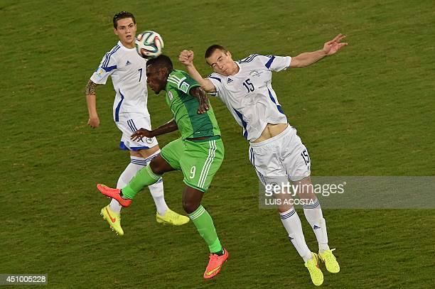 BosniaHercegovina's defenders Muhamed Besic and Toni Sunjic challenge Nigeria's forward Emmanuel Emenike as he jumps to head the ball during the...