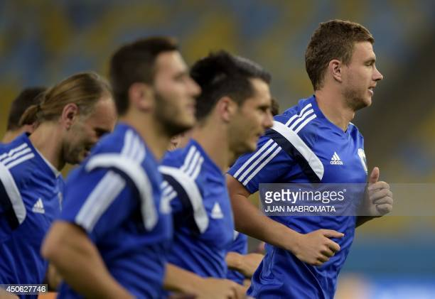 BosniaHercegovina's forward Edin Dzeko jogs next to teammates during a training session at Maracana stadium in Rio de Janeiro Brazil on June 14 2014...