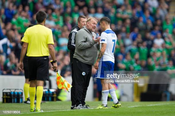 Bosnia-Herzegovina Head Coach Robert Prosinecki discusses tactics with Muhamed Besic of Bosnia and Herzegovina after their side go 1-0 up during the...