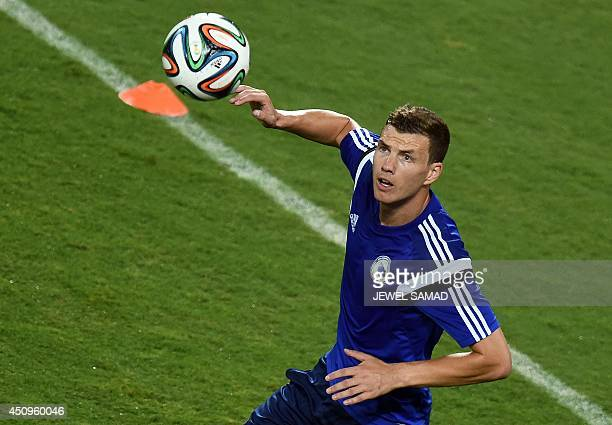 BosniaHerzegovina's forward Edin Dzeko prepares to head a ball during a training session at the Pantanal Arena in Cuiaba on June 20 on the eve of...