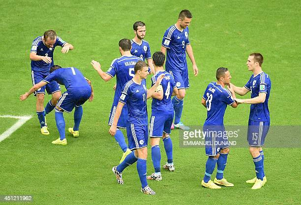 BosniaHerzegovina's midfielder Avdija Vrsajevic celebrates scoring his team's thrid goal as his teammates react during a Group F football match...