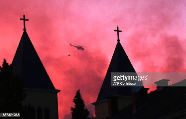 A Bosnian armed forces helicopter discharges water bucket while fighting against a forest fire near SouthernBosnian town of Capljina on August 22...