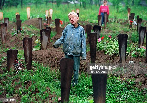 A Bosnian boy stands 06 May 1994 among the 200 graves in the Muslim cemetery in Ograndjenavac Bosnia On the seventh of May the Bosnian Croats and the...