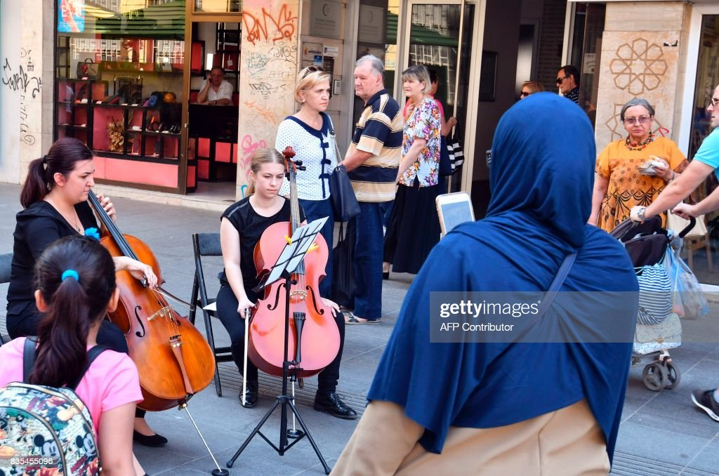 Bosnian cellists, Nejla Komar (L) and Fatima Muhedinovic (R) play Adagio in G-minor by Tomaso Albinoni, in central Sarajevo, on August 19, 2017, in tribute to the victims of the Spain's terror attacks. The same piece was played on La Rambla square in Barcelona in tribute to the victims of the Sarajevo siege during the Bosnian war in 1992-95. /