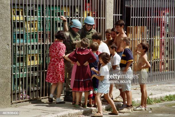 Bosnian children laugh with UN soldiers on August 10, 1993 in a street of Sarajevo.
