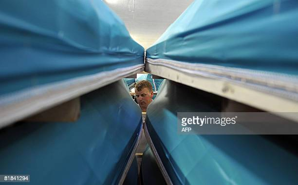 A Bosnian city morgue employee in centralBosnian town of Visoko seen through rows of coffins sorts names for 307 bodies to be transported and burried...