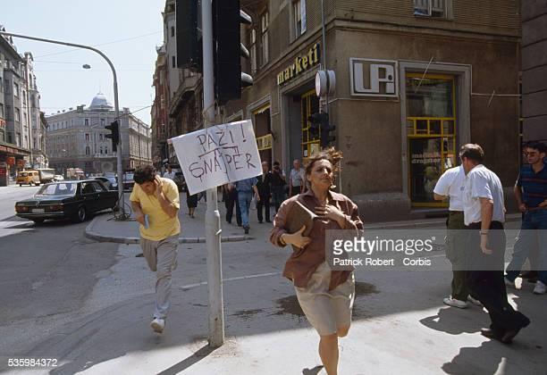 Bosnian civilians flee a sniper's gunshots on the streets of Sarajevo. Thousands of Bosnian and Serb civilians were victims of the Yugoslavian Civil...