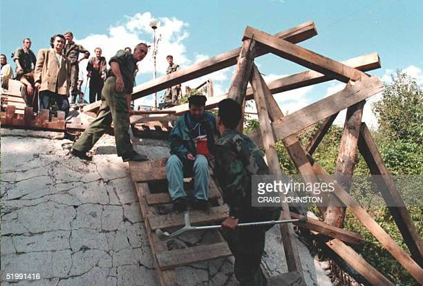 Bosnian Croat soldier holding the crutch of a local resident helps him over a makeshift crossing on the River Una west of Bihac Bosnia 20 September...