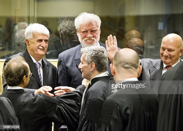 Bosnian Croats Bruno Stojic Slobodan Praljak and Milivoj Petkovic greet their lawyers in the courtroom on May 29 2013 before their sentencing at the...