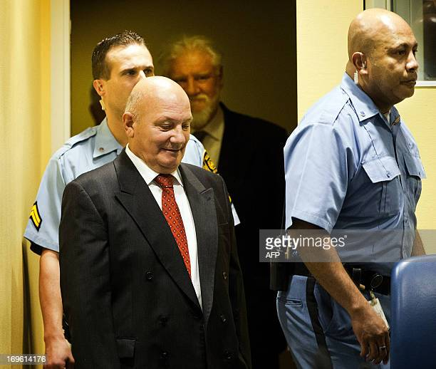 Bosnian Croats Milivoj Petkovic and Slobodan Praljak enter the courtroom on May 29 2013 before their sentencing at the International Criminal...
