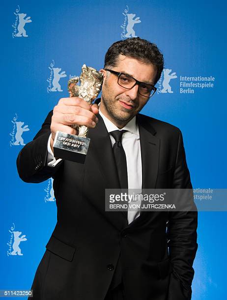 Bosnian director Danis Tanovic poses with his Sthe Silver Bear Grand Jury Prize trophy for his film 'Death in Sarajevo' during a photocall at the...