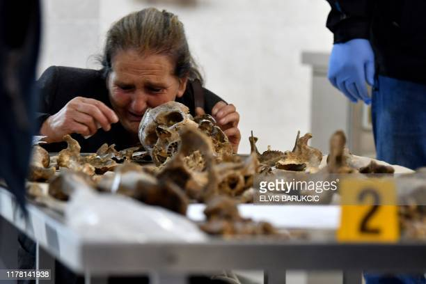 A Bosnian elderly woman cries near a human skeleton identified as her missing son's one during an identification process of remains found in a...