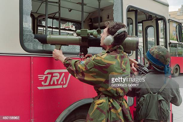 A Bosnian fighter aims its rocket launcher through the broken windows of a public bus during heavy fightings in the western suburbs of Sarajevo on...