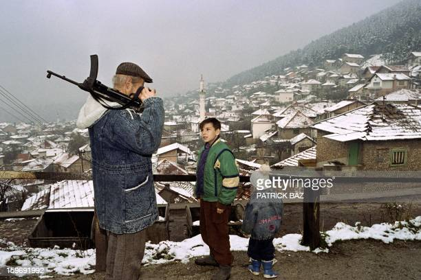 A Bosnian fighter views Sarajevo's Old City covered with snow on November 19 1992 AFP PHOTO PATRICK BAZ