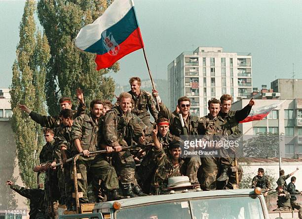 Bosnian government soldiers atop a truck wave a captured Serb flag in Zenica Wednesday Oct. 11 1995. The troops were coming back to their base in...