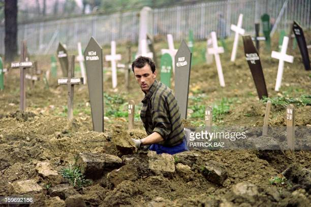 A Bosnian grave digger excavates in a football stadium in Sarajevo widening the main cemetery on November 05 in Sarajevo Christians and Muslims are...