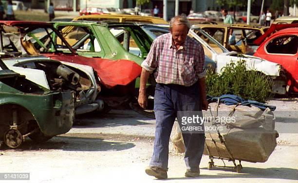 Bosnian man pulls his belongings on a luggage trolley 23 August 1993 as he walks past a parking lot full of car wrecks, on Alipasino Polje Avenue,...