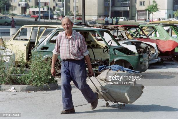 """Bosnian man pulls his belongings on a luggage trolley as he walks past a parking lot full of car wrecks,on Alipasino Polie Avenue, the """"saftest""""..."""