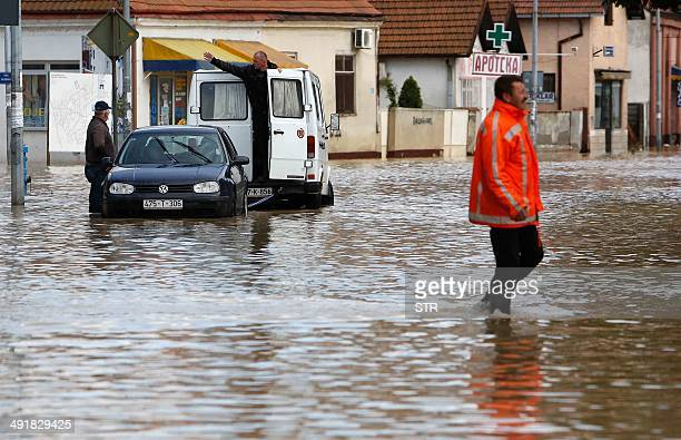 A Bosnian man walks in a flooded street in the EasternBosnian town of Bijeljina on May 17 2014 The heaviest rains in more than a century have sparked...